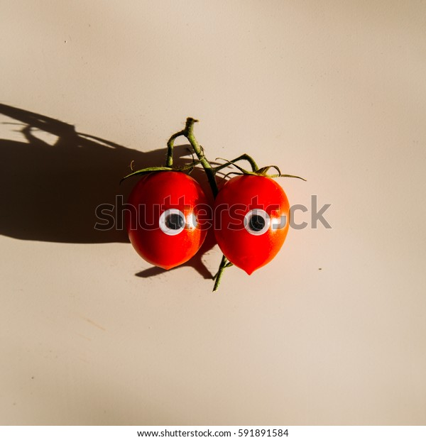 red little tomatoes on brilliant pastel background, minimal and shadow theme healthy food concept