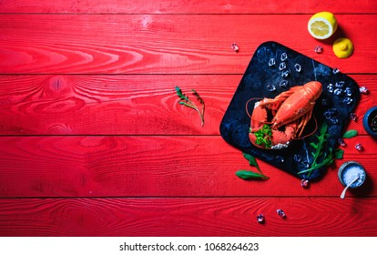 Red lobster with a bouquet of parsley in a clove, small white snails grown on the lobsters shell, on a black stone tray on red wooden background, top view, copy space