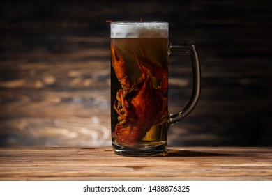 red lobster in glass with beer on wooden surface