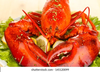 Red lobster on platter with vegetables on wooden table close-up