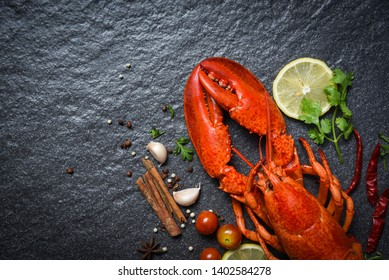 Red lobster seafood with lemon herbs and spices on dark backgroud top view copy space