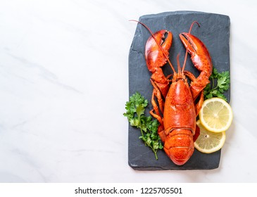red lobster with vegetable and lemon on black slate plate