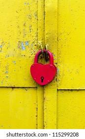 Red lock on a rusty yellow door