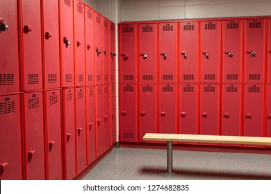 Red lockers in generic locker room with wooden bench