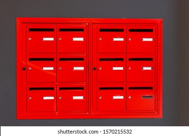 red lockers, many red mailboxes on a gray wall