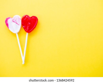 Red lollipop and white and pink lollipop on a yellow background