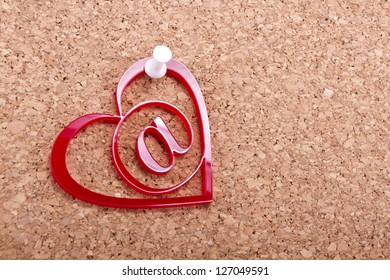 Red love email heart with white thumbtack on a cork board/Love email heart