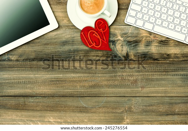 Red love heart, tablet pc, keyboard and coffee on wooden table. Valentines Day workplace. Retro style toned picture
