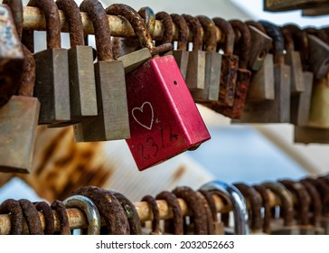 Red love lock with heart drawing, hanging on the bridge among other rusty locks.