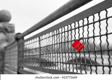 Red love lock padlock with heart on bridge symbol of true eternal love and commitment. Black and white stock photo with selective color effect.