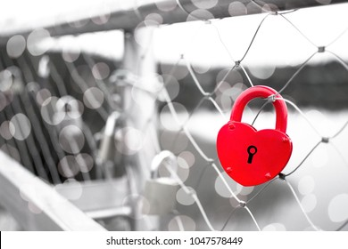A red love padlock fastened to a bridge railing isolated on black and white background