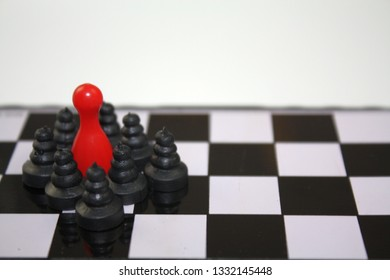 Red ludo figurine on chessboard black and white board with chess pawns