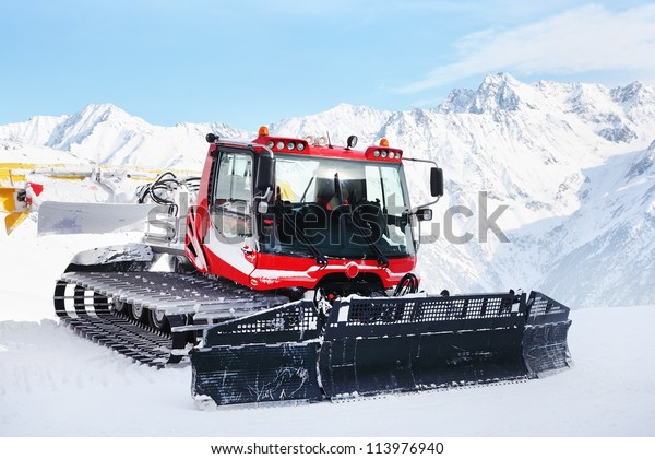 Red machine for skiing slope preparations in Austrian Alps at background of mountains.