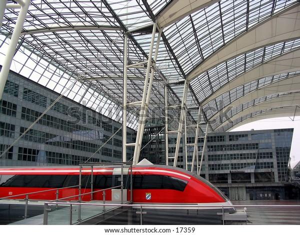 Red magnetic levitation train against futuristic buildings