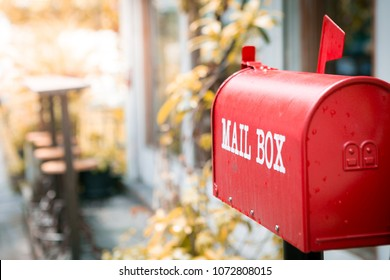 Red mailbox in front of the house with sunlight and beautiful natural background