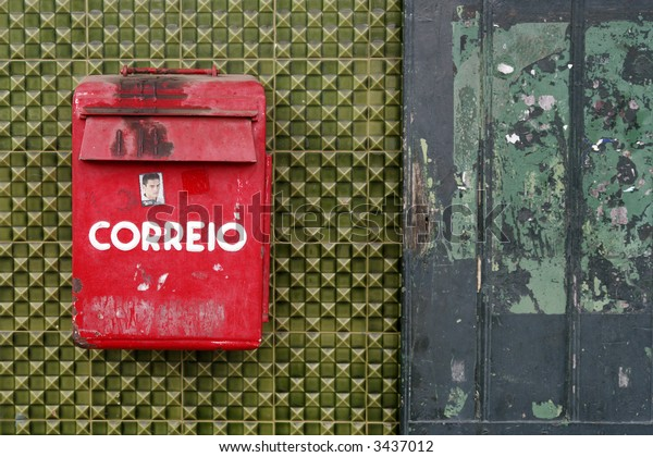 "Red mailbox on green wall with portuguese text ""Post"""