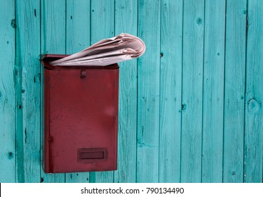 Red mailbox overflowing with newspapers on blue wooden wall