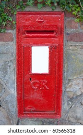 A red maillbox on a stonewall.