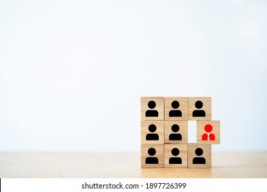 Red manager icon outstanding from staff employee icon which print screen on wooden block , different thinking and human development concept.
