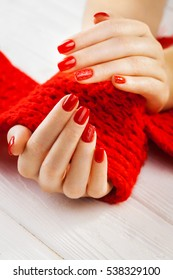 red manicure with a red knitted scarf on the white wooden table.
