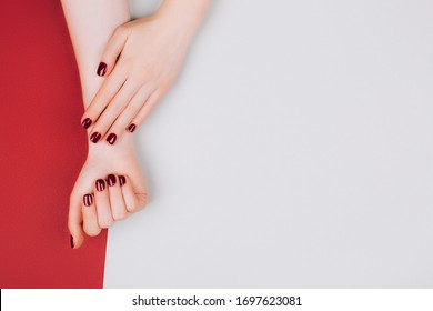 Red manicure on beautiful accurate woman's hands. Stylish manicure and social distance concept. Flat lay style.