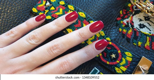Red manicure on a black leather and beads