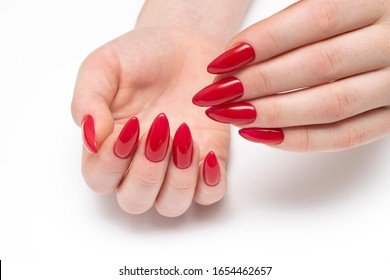 Red manicure on long sharp nails closeup on a white background. Red stilettos. Gel nails.