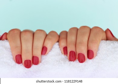 Red manicure on white towel