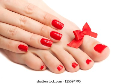 Red manicure and pedicure with a bow