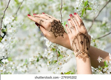 Red manicured hands with Mehndi in spring cherry blossom, Indian tradition. Horizontal composition.