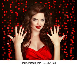 Red Manicured nails. Elegant brunette. Beautiful smiling girl with healthy curly hair style and lips makeup. Young woman showing ten fingers over party lights background.