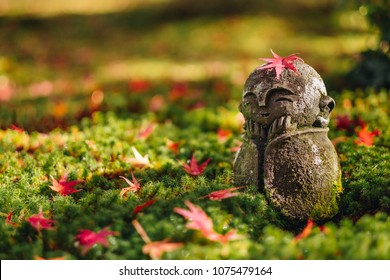 Red Maple leaf on head of Jizo  sculpture doll (little Japanese Buddhist monk doll rock) in Japanese Garden, Enkoji Temple, Kyoto, Japan. Autumn season japan