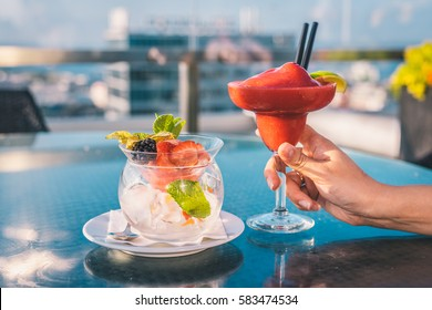 Red margarita cocktail in woman hand on the open terrace in coctail bar during summer time