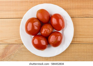 Red marinated tomatoes in white plate on wooden table. Top view