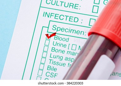 Red mark on test screening form with blood in tube for test.