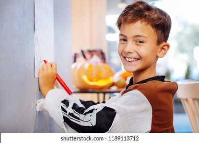 Red marker. Beaming dark-haired boy wearing Halloween costume holding red marker crossing dates in calendar