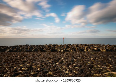 Red marker post on sea front with rocks in foreground and long exposure sea and clouds