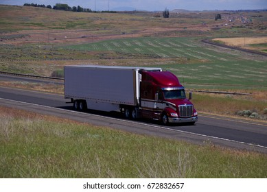 A Red / Maroon Peterbilt Semi-Truck pulling a white unmarked trailer along a rural Oregon Highway.  June 20th, 2017 Rural Oregon, USA