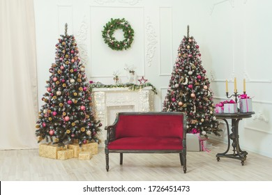 Red maroon sofa near the fireplace and Christmas trees. Balls ribbons garlands in rose gold maroon style decoration on Christmas tree. Beautiful Christmas decor of residential white room with stucco