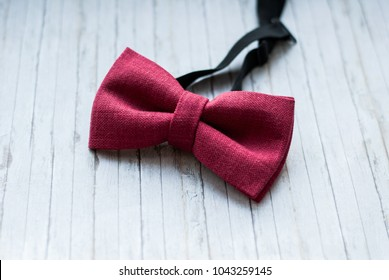 Red, marsala bow tie on a wooden background. Accessory for formal dress. Symbol of elegance and fashion for men. Men's casual. Men's and women's accessories. Men's and women's bowtie.