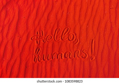Red Martian sand with the inscription hello, humans. Copy space. The message of the Martians to Earth.