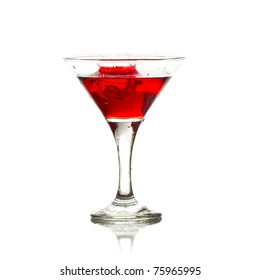 red martini cocktail splashing into glass on white background