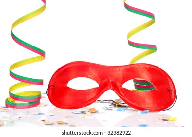 Red mask, ribbons and confetti on white background. Shallow depth of field