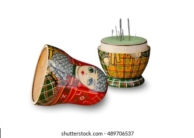 Red matryoshka doll-pincushion. Sewing needle. White background. Isolated