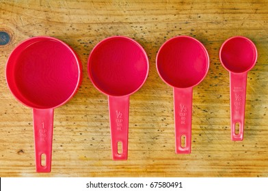 Red measuring cups in different sizes on a timber board