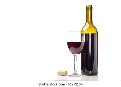 Red Merlot in a wine glass with bottle and cork.