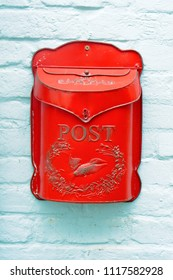 A red metal antique metal box on a blue stone wall