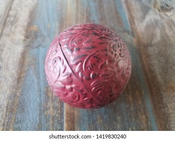 red metal ball on brown wooden table