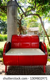 Red metal bench decoration and furniture in public garden park made from gas oil iron tank in Sing Buri, Thailand