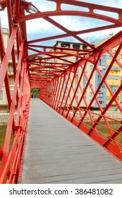 The red metal bridge over the river Onyar Eiffel in the historic center of Girona.